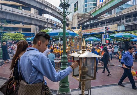 warship: Bangkok, Thailand - June 19, 2015 Unidentified tourist man prepares incenses to warship for The Lord Brahma Shrine at Grand Hyatt Erawan Hotel.