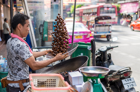 china town: Bangkok, Thailand - July 15, 2015 Unidentified man is cooking chestnut for sell in area of Yaowarat or Thailands China Town