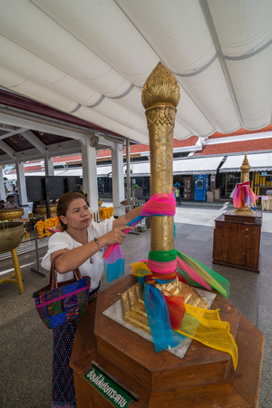 Bangkok, Thailand - Aug 10, 2015 Unidentified woman is offering colorful textile to The Bangkok City Pillar Shrine for making her wish. Editoriali