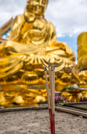 mit: Bangkok, Thailand - Aug 7, 2015 Burning joss stick in front of out door golden Buddha at Wat Trai Mite or Trai Mit Temple. Editorial