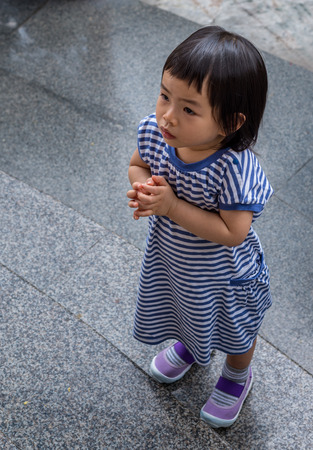 pays: Thai toddler girl pays respect to statue of Buddha