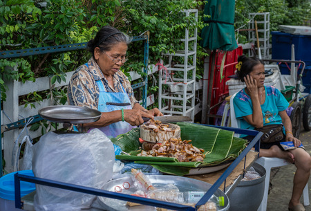 pra: Bangkok, Thailand - Sep 12, 2015 Unidentified old woman is selling bbq pork at Tha Pra or Tha Luang, the pier on the historic Rattanakosin of the Chao Phraya Rive