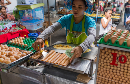 Bangkok, Thailand - Nov 14, 2015 Unidentified woman is selling Khanom bueang or Thais crepes at Chatuchak, the biggest weekend market in South East Asia.