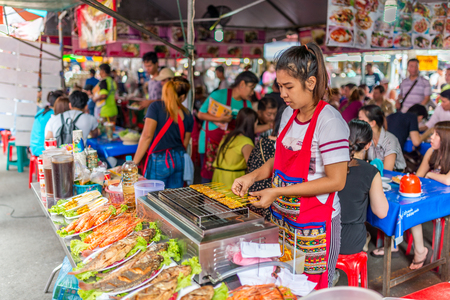 Bangkok, Thailand - Nov 7, 2015 Unidentified woman is selling Pork Satay or BBQ pork with curry powder and sea food at Chatuchak, the biggest weekend market in South East Asia. Editorial