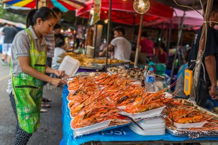 Bangkok, Thailand - Nov 7, 2015 Unidentified woman is selling grilled shrimp at Chatuchak, the biggest weekend market in South East Asia. Editoriali