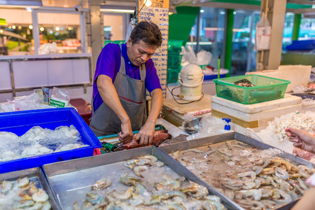 Bangkok, Thailand - Nov 14, 2015 Unidentified seller is cleaning fish for customer at Or Tor Kor market, a well known place for fresh food, fruits and foods. Located next to Jatujak market.