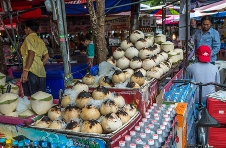 Bangkok, Thailand - Nov 7, 2015 Fresh coconut juice and Burned coconut juice for sell at Chatuchak, the biggest weekend market in South East Asia.