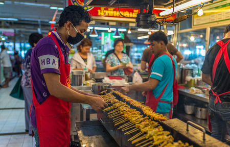 Bangkok, Thailand - Nov 14, 2015 Unidentified man is grilling pork satay for sell at Or Tor Kor market, a well known place for fresh food, fruits and foods. Located next to Jatujak market.