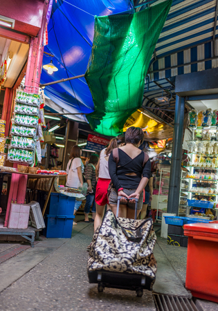 Bangkok, Thailand - Nov 7, 2015 Unidentified tourist is draging a big bag for shopping at Chatuchak, the biggest weekend market in South East Asia.
