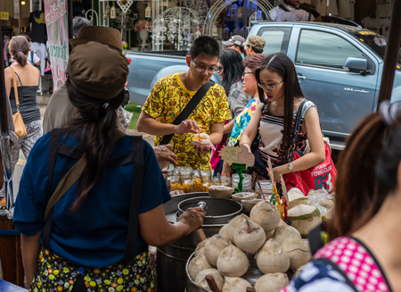 Bangkok, Thailand - Nov 7, 2015 Unidentified tourist is buying Fresh-coconut-ice cream at Chatuchak, the biggest weekend market in South East Asia.