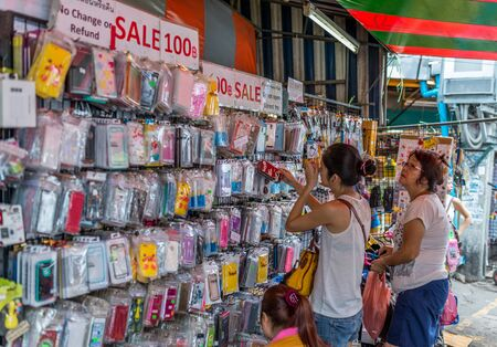 Bangkok, Thailand - Nov 7, 2015 Unidentified tourist is buying inexpensive cellphone case at Chatuchak, the biggest weekend market in South East Asia.