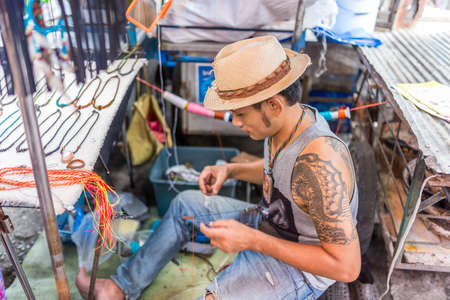Bangkok, Thailand - Nov 14, 2015 Unidentified man is making textile necklace for sell on street of Chatuchak, the biggest weekend market in South East Asia.