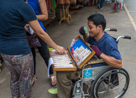 Bangkok, Thailand - Nov 7, 2015 Unidentified man on wheel chair is selling lotterry at Chatuchak, the biggest weekend market in South East Asia.