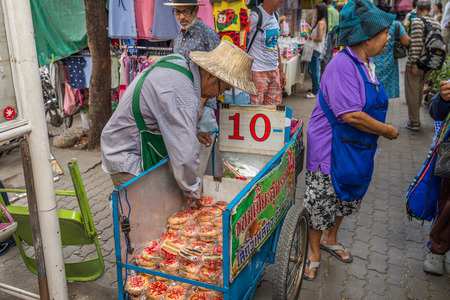 Bangkok, Thailand - Nov 14, 2015 Unidentified old couple is selling cake sphare  on street of Chatuchak, the biggest weekend market in South East Asia. Editorial