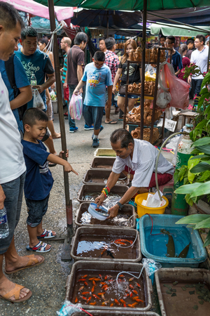 Bangkok, Thailand - Nov 14, 2015 Unidentified man is selling fish at Chatuchak, the biggest weekend market in South East Asia.