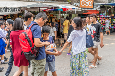 Bangkok, Thailand - Nov 14, 2015 Unidentified tourist is opening guide book at Chatuchak, the biggest weekend market in South East Asia. Editorial