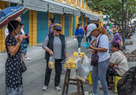 tha: Bangkok, Thailand - Dec 10, 2015 Unidentified tourist is buying pineapple on sidewalk at Tha Luang, the area of food and pier next to The Grand Palace