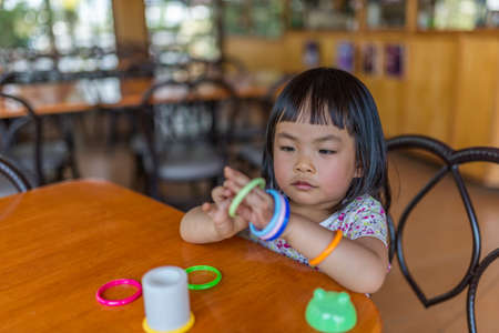 resturant: Asian toddler girl in happy time with ring toy while waiting food in a resturant Stock Photo