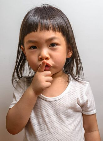 shh: Little girl with gesture shh
