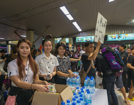 Bangkok, Thailand - Oct 18, 2016 Unidentified volunteer university students come to give free water and snacks for people who come to pray for the dead king at Bangkok Railway Station, unofficially known as Hua Lamphong Station Editorial