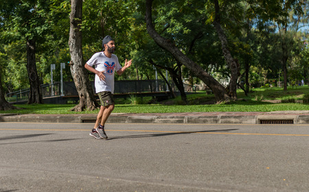 Bangkok, Thailand - Nov 13, 2016 Unidentified old man is jogging in Lumpini Park, the most public park in the downtown Editorial