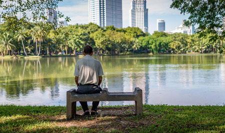 Bangkok, Thailand - Nov 13, 2016 Unidentified old man is sitting alone  in Lumpini Park, the most public park in the downtown