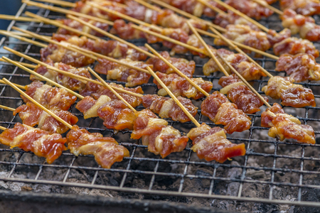 Traditional bbq pork is be cooking for sell on street food of Bangkok, Thailand