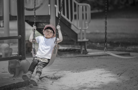 Color adjusted image for lonely mood of  little girl is lonely on swing in a public park