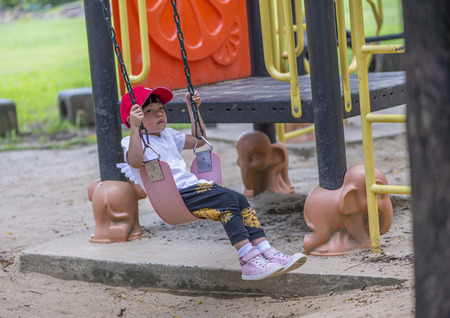Moody Asian little girl plays swing in a playground