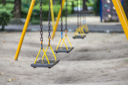 Old swing in a playground in lonely mood Stock Photo