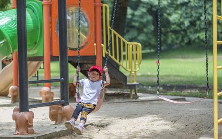 Little girl is lonely on swing in a public park