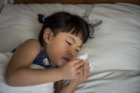 Weinig Aziatisch meisje in bed kijkt naar weefselpapier met haar loopneus