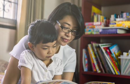 Asian Mother read book with daughter in bedroom