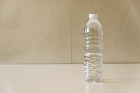 One Bottle of water on white table in a room with white wall.