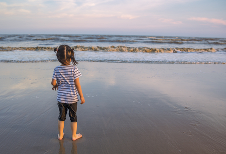 Asian little girl standing on the beach in sunset. Eyes looking to the sea. Image from behind the girl. Beautiful sunset time, reflex on the beach and colorful sky. Stock fotó