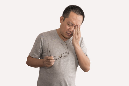Asian man having eye pain with migraines. Holding eyeglasses, image is on isolated white background. Man is 40-45 years old.