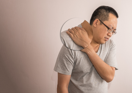 Middle aged Asian man having shoulder pain. Man wear eyeglasses. Use one hand touch shoulder.