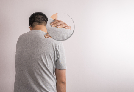 Asian man having shoulder pain. Image from back side. Design focus pain area bigger than usual. Use one hand touch shoulder.