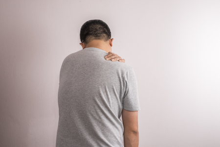 Asian man having shoulder pain. Image from back side. Use one hand touch shoulder.