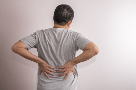 Asian man with backache. Pain relief concept. Man on blank wall.