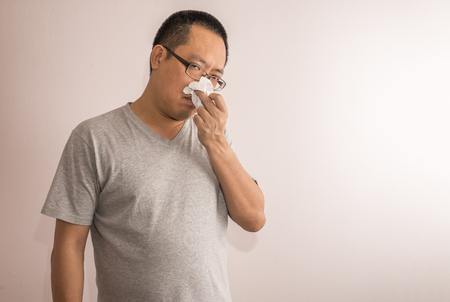 Asian or Thai  man affected by common cold. Using tissue paper cover his nose. Looking at camera. Stock fotó