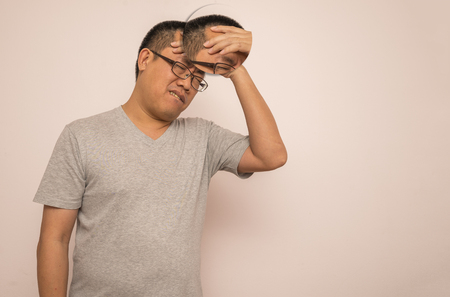 Asian man having a headache. Face show painful. Middle aged man wear eyeglasses. Use one hand on forehead. Creative concept.