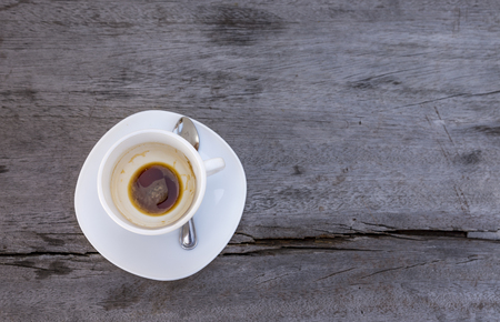 Top view empty cup of coffee after drink on wooden old table. White coffe cup with spoon. Old wood table with crack on surface. Space for text.