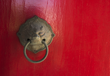 Ancient door knocker in Asian or Chinese tradition art on red wood door. Ancient dragon door knocker, close up image. Space for text.
