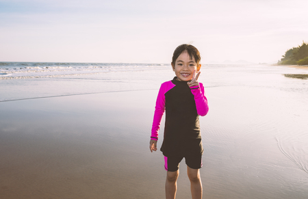 Attractive adorable Asian little girl in long sleeve swimming suit on the beach in sunset. Girl shows victory gesture for confidence. Big smiling face. Space for text.