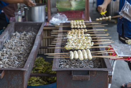 Tradition Thais snack, grilled or toasted banana. Banana with wood stick for holding. Image of local organic food market in Thailand.