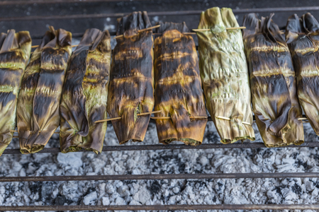 Sticky rice in banana leaf grill on charcoal at organic food market of thailand. Close up pack of grilled sticky rice in banana leaf in a row. Space for text.