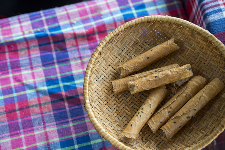 Tong Muan, a type of rolled wafer with black sesami, a traditional snack in Thailand. Snack in Wicker basket. Top view image with space for text.