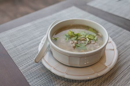 Rice soup in a white bowl on table. Natural light in a morning. Breakfast with rice soup with pork, topping with green vegetable - coriander and celery. Stock fotó