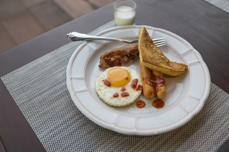 Breakfast dish on wooden table. Fried egg, bacons, sausages and potato bread. Topping with spicy sauce. Aluminium on dish, one organic glass of plain yogurt.